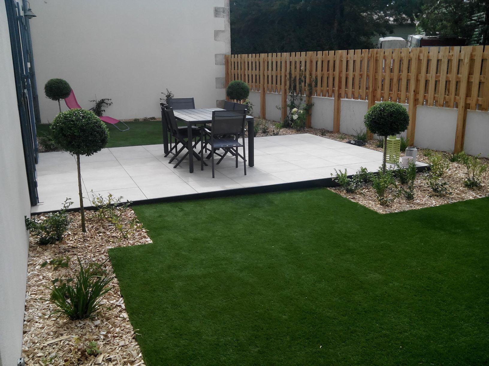 Petit extérieur de maison avec terrasse carrelée, table à manger, pelouse et parterres avec plantes et arbustes