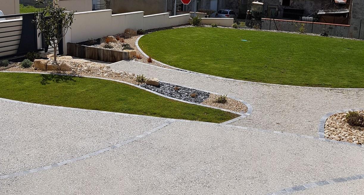 Allée d'entrée de pavillon structurée et gravillonnée avec espace pelouse et massif rocailleux